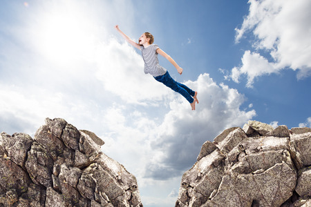 Little cute girl flying like a supergirl from one rock to another.