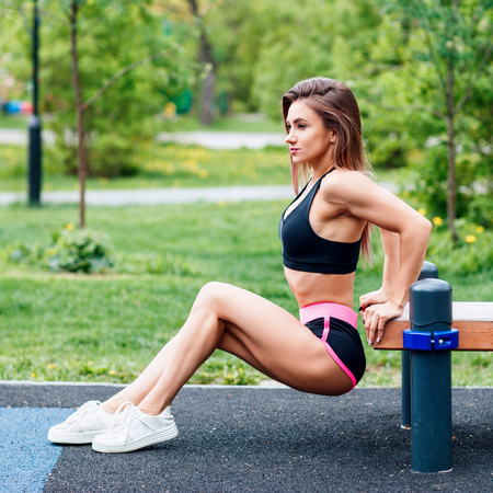 Young sporty woman doing triceps dip exercise on city street bench.