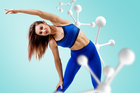 Athletic fitness woman standing near white molecule chain. 版權商用圖片