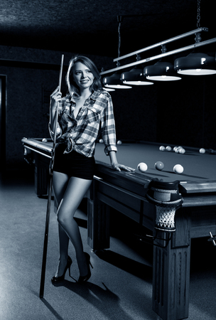 Beautiful woman stands near billiards table with cue.