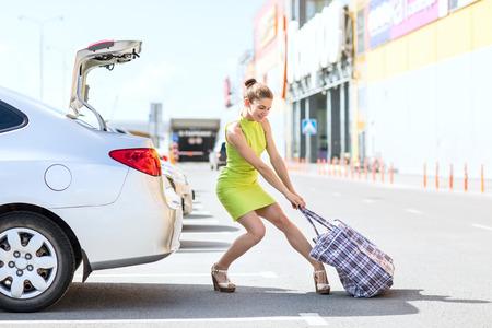 Mujer elegante houls pesado bolso grande al maletero del coche en día de verano.