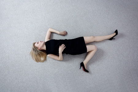 Beautiful dead woman in black dress lying on the floor.
