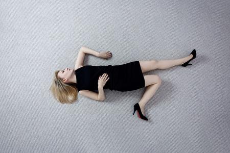 Belle femme morte en robe noire allongée sur le sol. Banque d'images