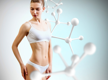 Woman with perfect body near big molecule chain. Slimming concept.