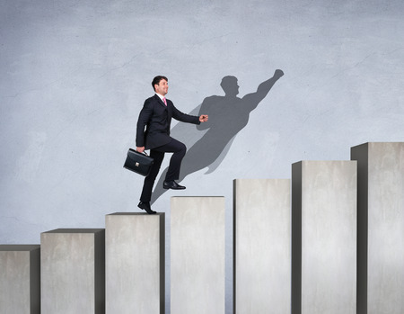 Businessman rise up on the career ladder with superhero shadow on the wall.