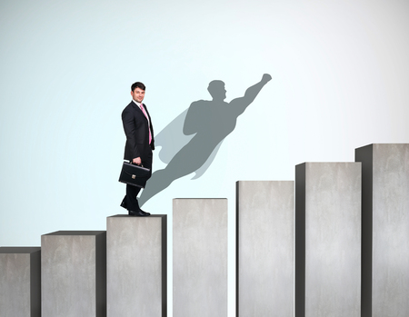 Businessman rise up on the career ladder with superhero shadow on the wall. Banco de Imagens - 111567460