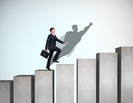 Businessman rise up on the career ladder with superhero shadow on the wall. Banco de Imagens - 112529924