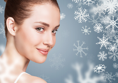 Young woman over blue backgroud with snowflakes.