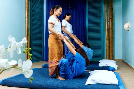 Two thai masseuses synchronously doing thai massage.