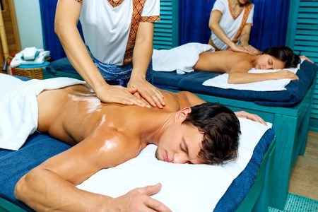Young couple having thai massage with an oil.