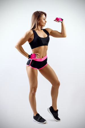 Young woman in sportswear demonstrated her beautiful muscular athletic body. Stock Photo