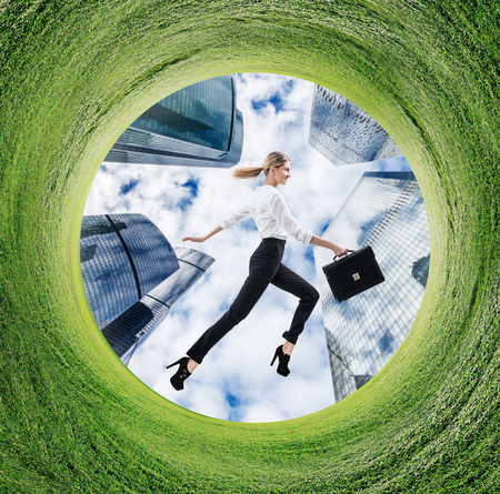 Business woman running in rotated field with green grass.