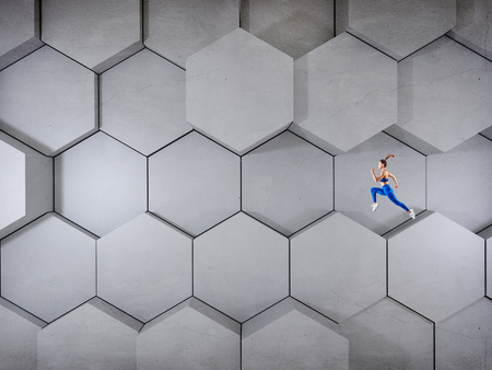 Woman jumps over gray hexagons background.