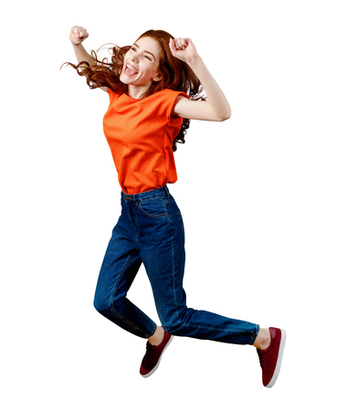 Full length happy ginger woman in shirt and jeans jumping.
