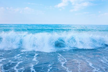 Hermosa vista de salpicaduras de olas azules cerca de la playa.