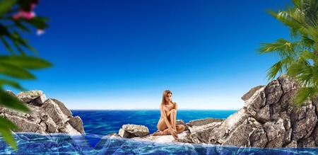 Naked woman sitting on rock among sea.