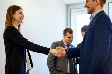 Young business woman and man in formal wearing shaking hands foeground view. Imagens