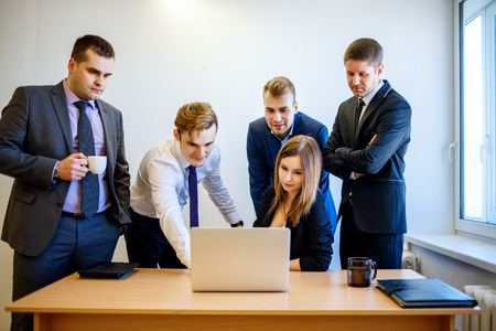 Woman sitting at the desk, the team is standing around her.