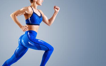 파란색 운동복을 입은 젊은 여성 주자가 공중에 뛰어듭니다.