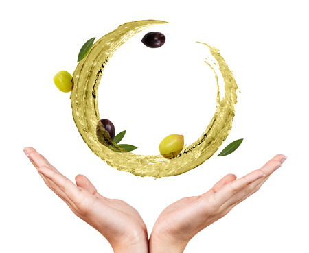 Circulate splash of olive oil with olives in female hands.