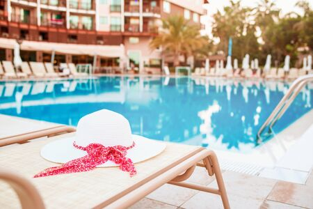 Summer hat lying on deck chair in front of swimming pool.