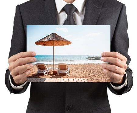 Businessman holds placard with  of vacation scenery. Imagens