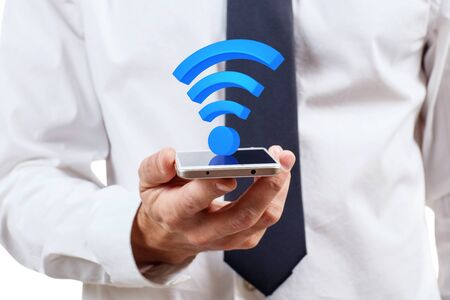 Businessman demonstrate big virtual wifi icon from smartphone.