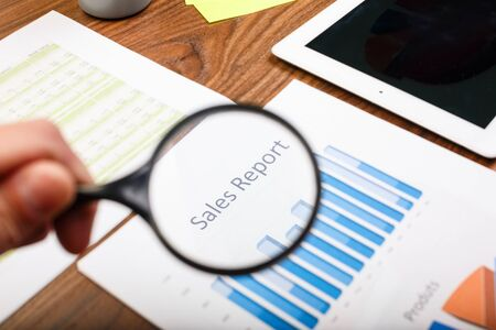 Hand holds magnifying glass over paper with sales report.