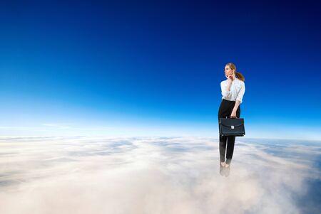 Young businesswoman in formal wear flying in blue sky.