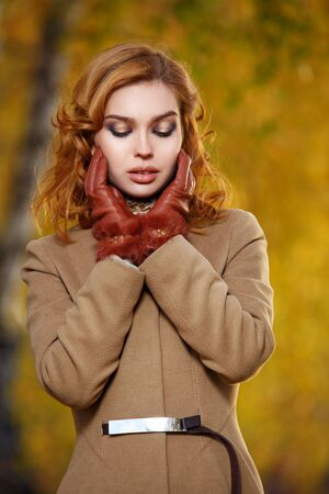 Stylish woman in beige coat and gloves standing in autumn yellow park.