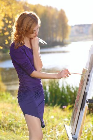 Young woman in sexy dress painting outdoors in autumn park. Reklamní fotografie