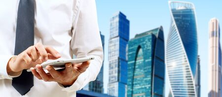 Businessman using tablet computer over cityscape background