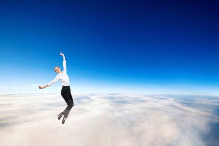 Businesswoman in formal wear flying in blue sky.