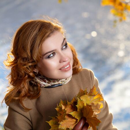 Young woman in the park and holds yellow autumn maple leaves.