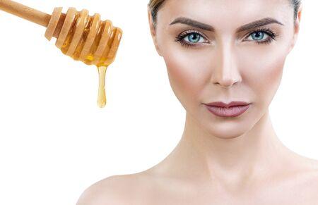 Beautiful woman near honey prepare for honey facial mask. Imagens