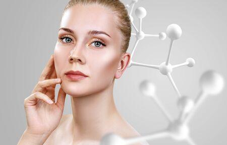 Beautiful young woman near big white molecule chain. Imagens
