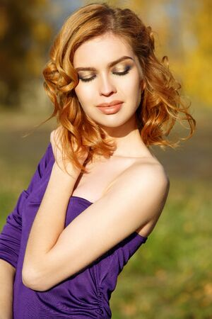 Beautiful woman in purple dress posing in autumn time. Imagens