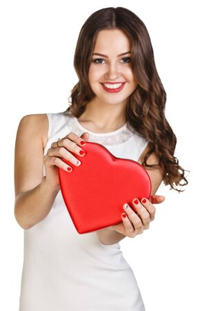 Young woman in white dress holds heart shaped box. Imagens
