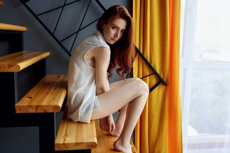 Redhead woman sitting on the staircase in loft apartment.