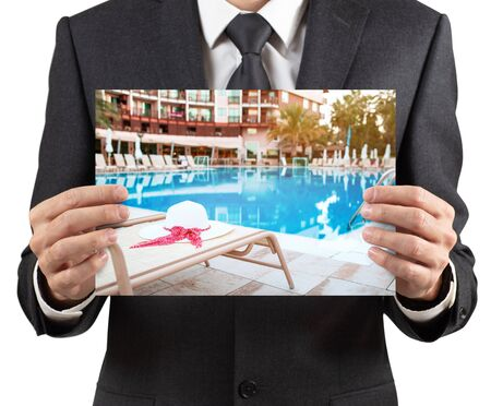 Businessman holds placard with photo of vacation scenery.