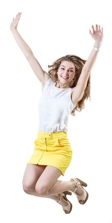 Happy young woman in yellow skirt jumps up. Imagens