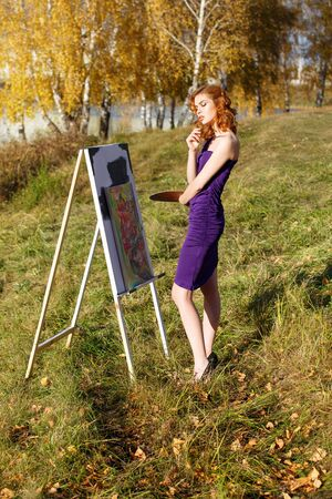 Beautiful woman in purple dress painting outdoors in autumn park.