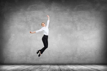 Happy young woman in formal wear jumps up.
