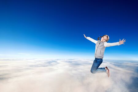 Little girl flying over clouds in the blue sky. Imagens