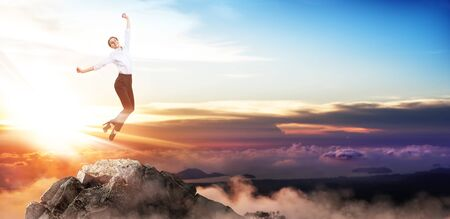 Happy business woman jumps up on mountain peak.