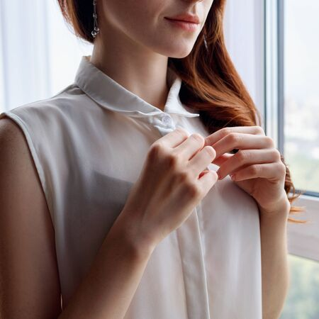 Redhead woman unbuttoning white blouse at home.