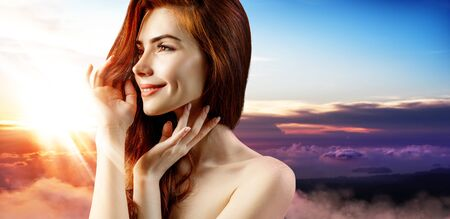 Redhead woman over beautiful colorful sunset.