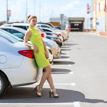 Successful woman standing nead car on shopping center parking.