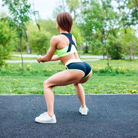 여름 공원에서 쪼 그리고 앉는 운동복에 스포츠 소녀.