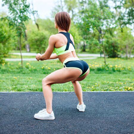 Sportowa dziewczyna w sportowej kucki w parku latem.